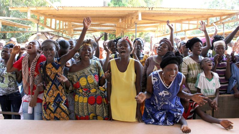 Group of African women galvanized by prayer, almost in a trance.